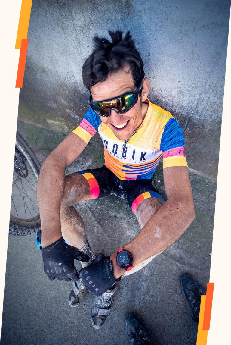 Sergio Bike entrenador de ciclismo sonriente sentado en el suelo después de una carrera